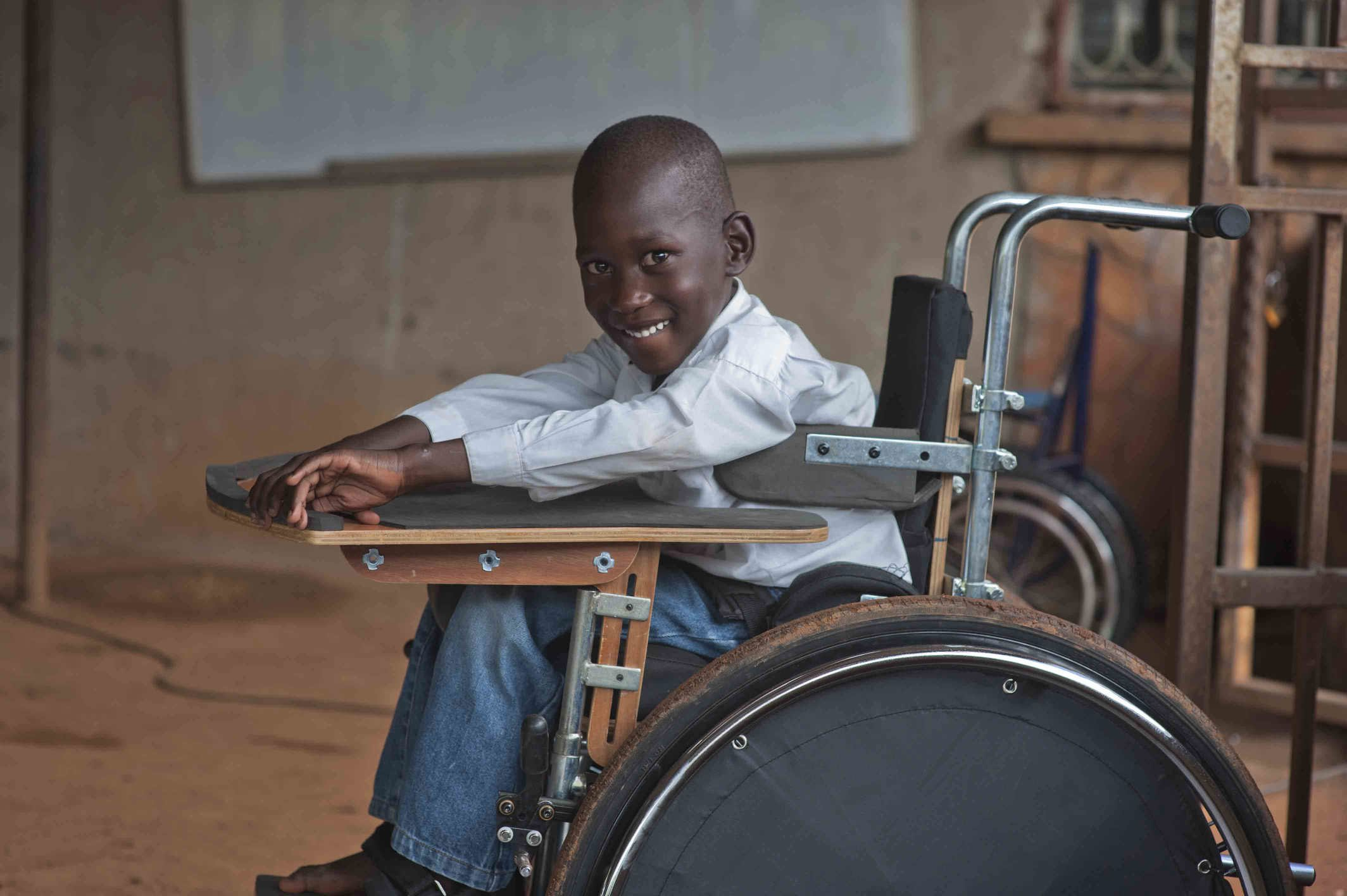 A young child from Uganda in a Motivation wheelchair at school, leaning forward and smiling