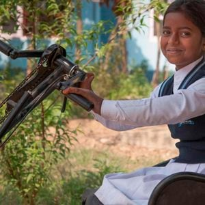 Young girl in India sitting in a hand-propelled tricycle